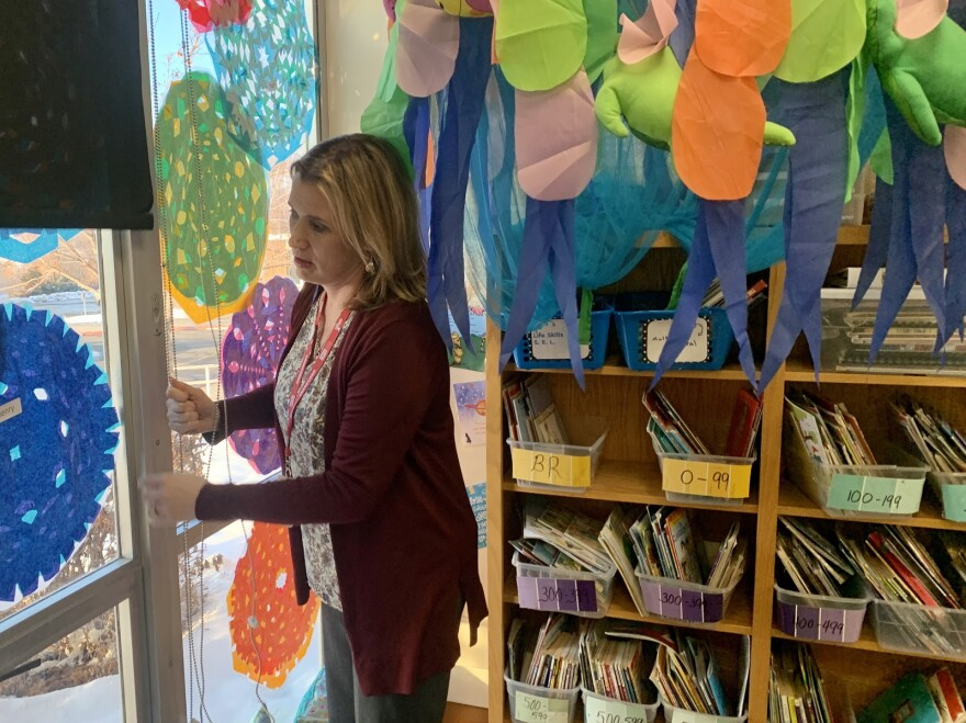 Woman looks out window in colorful classroom.