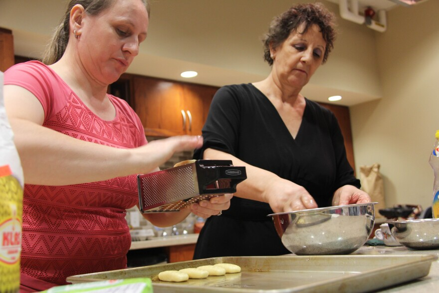 Two Bosnian women demonstrate how to make hurmasica, a popular Bosnian dessert, at a cooking workshop given at Fontbonne University in November 2017.