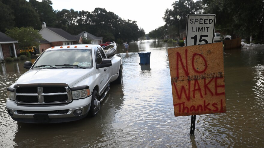 """A """"no wake"""" sign is seen along side a street in a residential neighborhood inundated with floodwaters this week in Sorrento, La."""
