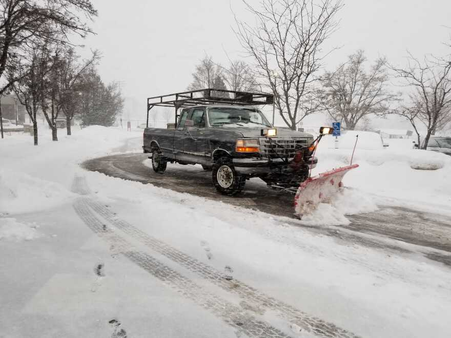 Photo of a black truck plowing snow.