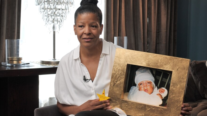 A photo of Cheryl Martin holding a picture of her son, Colin Martin.