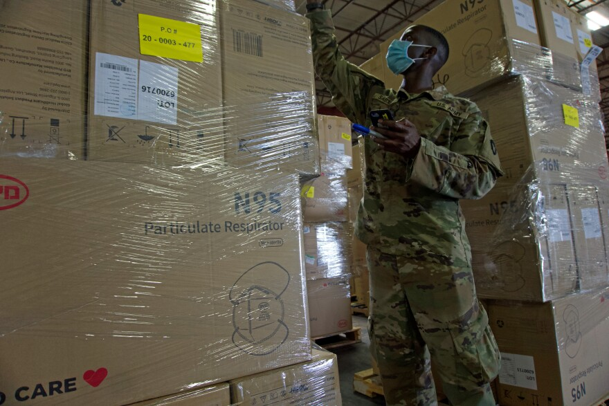 Military personnel stock Personal Protective Equipment (PPE) at the Texas Department of Emergency Management warehouse in San Antonio.