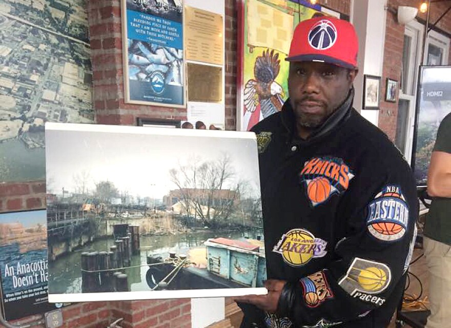 Anthony Satterthwaite, one of the original Earth Conservation Corps members, holds up a photograph of what part of the Anacostia River looked like in 1992.