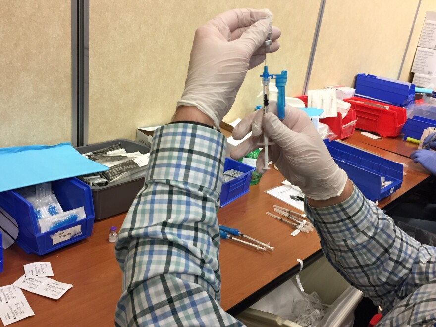 A person wearing a plaid long sleeve shirt and white gloves fills a syringe with Pfizer's COVID-19 vaccine over a table laden with alcohol swabs, more syringes and other supplies.