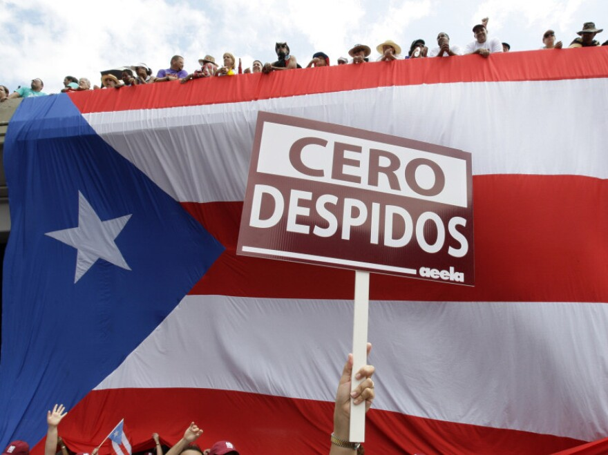 """A demonstrator holds a sign that reads in Spanish """"Zero Layoffs"""" while marching in front of a giant Puerto Rican flag in San Juan in October 2009."""