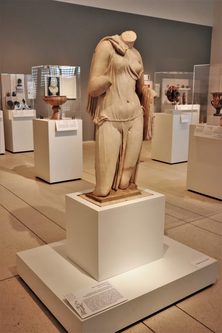 A marble statue of the torso of Aphrodite or Venus stands among ancient pottery.