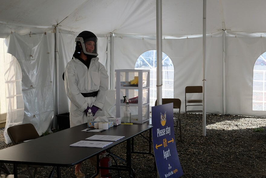 A health care worker in personal protective equipment stands in a COVID-19 testing site for students at Montana State University, Bozeman, September 01, 2020.