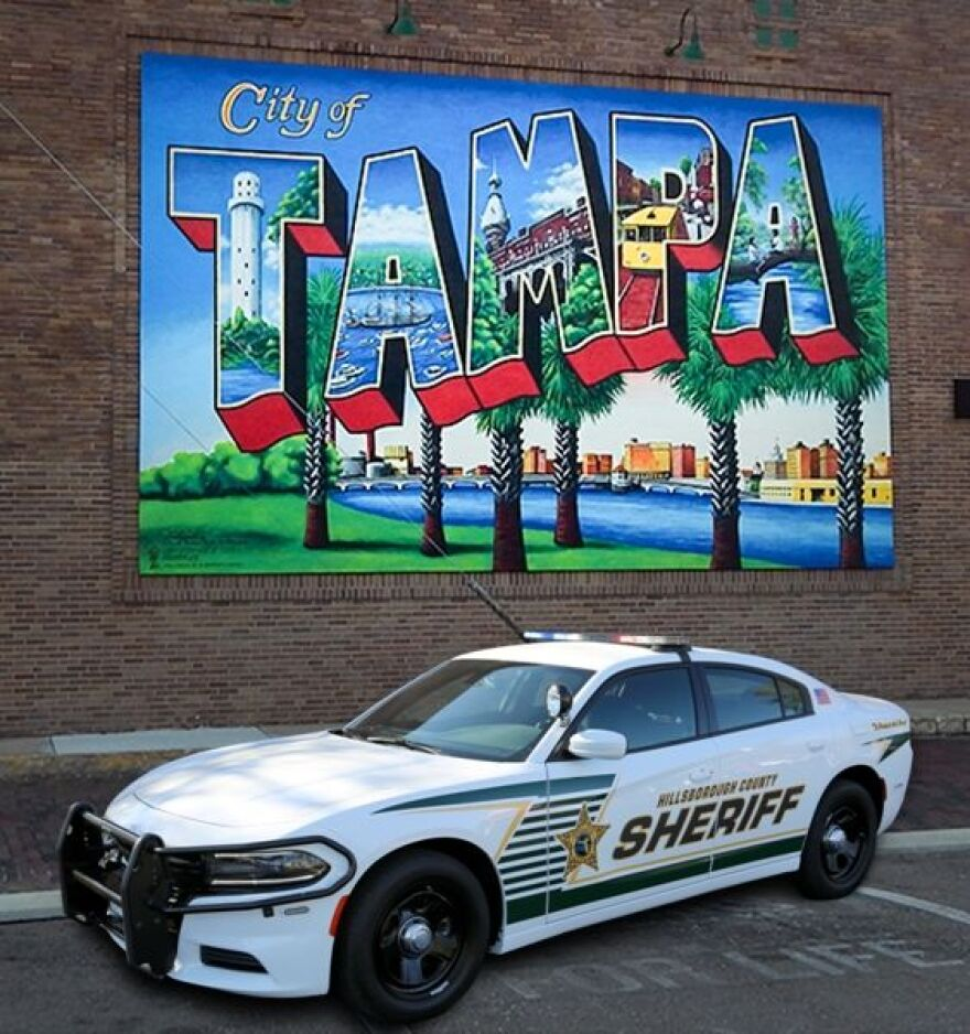 Hillsborough County Sheriff cruiser parked in front of brick wall that has a postcard of Tampa.