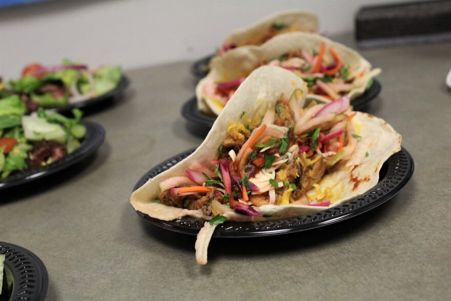 Three black plates on a grey surface. Two of the plates have tortillas with filling.