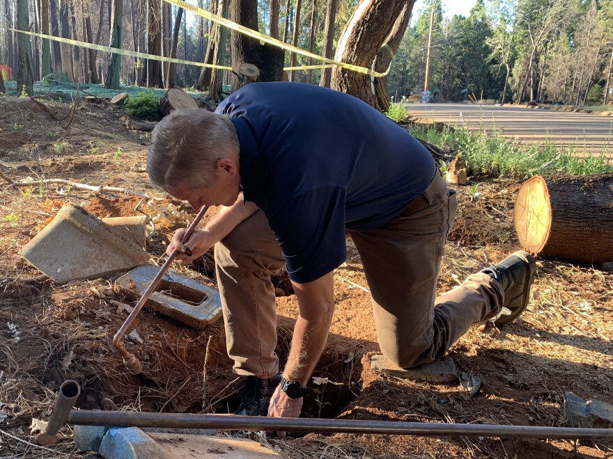 Jim Roberts, assistant superintendent at Del Oro Water Company, has lived and worked in Magalia for 40 years. He taps a water main to take a sample on a burned property.