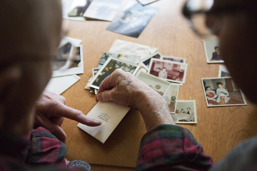 Stanley looks at old photographs with his sons. He's 91 now, but his voice sounds nearly the same as it did on the tape.