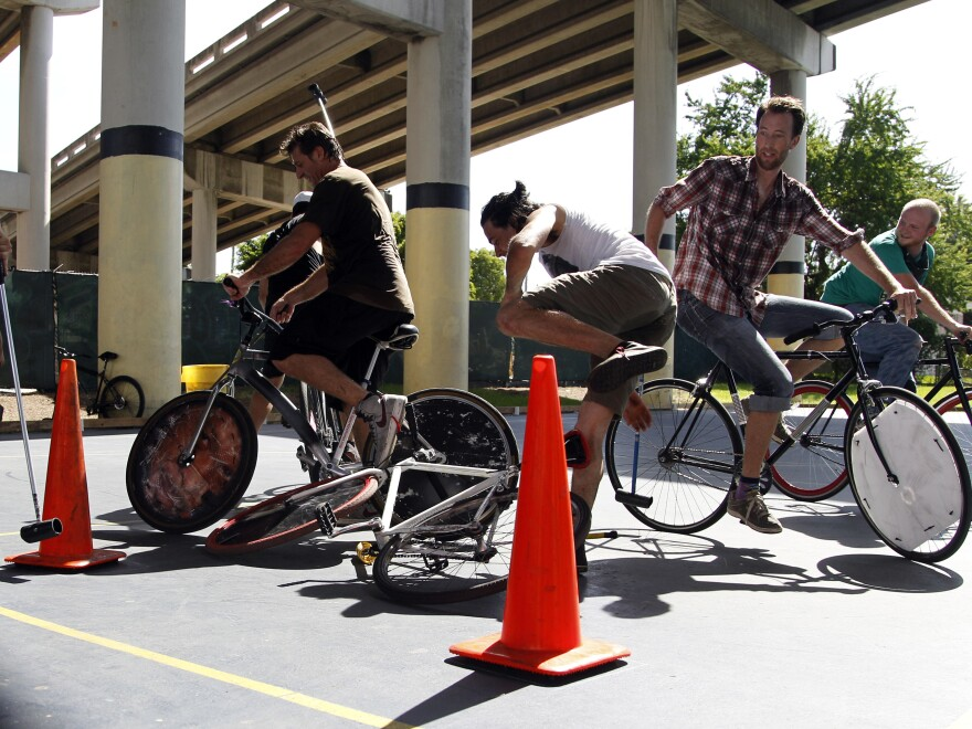 Bruno Rodriguez (center) falls from his bike while playing hard-court bike polo at Jose Marti Park in Miami on Sunday. The game can be brutal, and players often leave with scrapes and bruises.