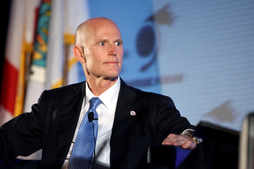 Governor Rick Scott in his office in front of a Florida flag