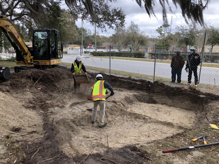 Workers dig up a gravesite