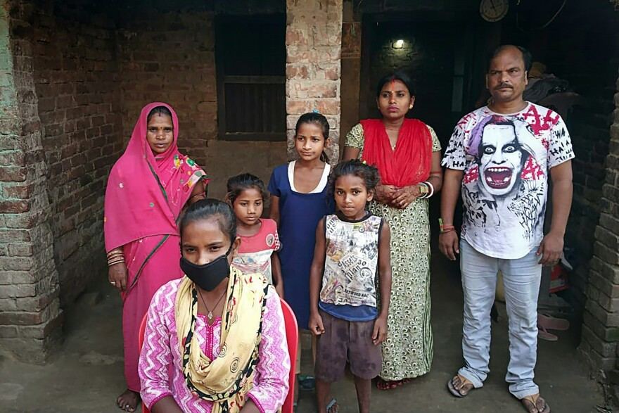 Jyoti Kumari (center, foreground, in mask) and family members stand in front of their house in Siruhulli, a village in eastern India.