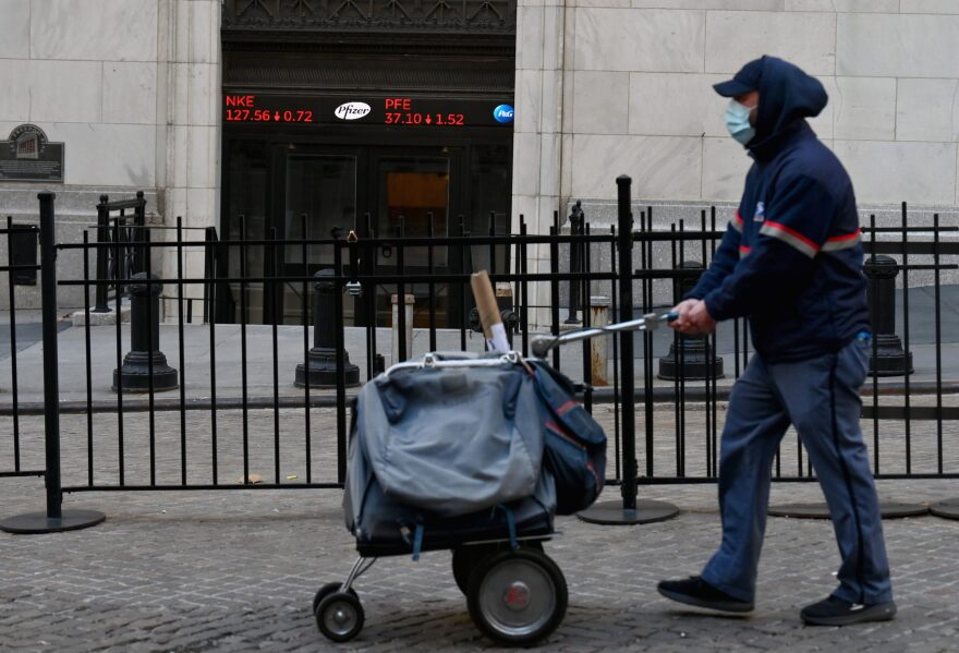 A USPS mail carrier walks past the New York Stock Exchange (NYSE) at Wall Street on Nov. 16, 2020 in New York City. - Wall Street stocks rose early following upbeat news on a coronavirus vaccine and merger announcements in the banking and retail industries. (Angela Weiss/AFP via Getty Images)