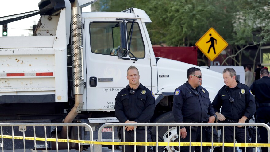 Phoenix police officers stand beside a dump truck blocking a road outside the Phoenix Convention Center on Aug. 22. Protests were held against President Trump as he planned to host a rally inside the convention center.