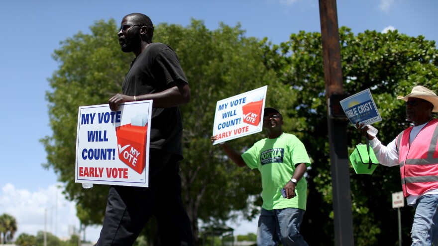 Voters walk to an early voting site to cast their ballots on Aug. 11 in Miami. On Wednesday, a federal appeals court in Ohio upheld a decision extending early voting in that state. Meanwhile, as Election Day nears, courts are still considering cases about early voting in North Carolina, and voter ID requirements in Texas and Wisconsin.