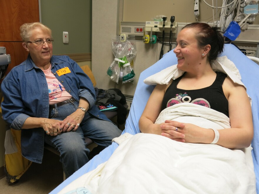 Ashley Copeland (right) talks to her mom Sue Iverson in the Swedish Medical Center emergency department, near Denver. Copeland got a nerve-blocking anesthetic instead of opioids to ease her severe headache. At discharge she was advised to use over-the-counter painkillers, if necessary.