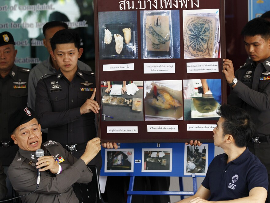 Policemen show pictures of body parts found in parcels as they address reporters in Bangkok on Monday. Thai police said two Americans who had tried to send the parts to the U.S. had fled the country.