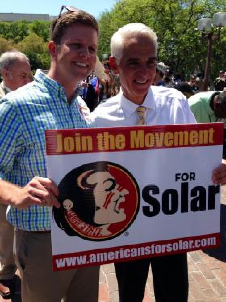 NEW FRIENDS: Crist helps a student spread the word about exploiting solar potential in Florida.