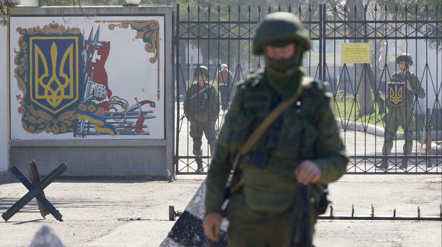 Russian soldiers guard the entrance to the Ukrainian military base in Perevalne, Crimea, last March. Russia was criticized widely internationally after seizing the region. Now Russian lawmakers are considering a bill that says Crimea was illegally given to Ukraine in 1954 and should have been part of Russia all along.