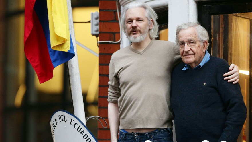 Julian Assange (left) is happy with a new offer from Sweden, his lawyers say. He's seen here with American linguist and writer Noam Chomsky on the balcony of the Ecuadorian Embassy in London, where the WikiLeaks founder sought refuge to avoid extradition.