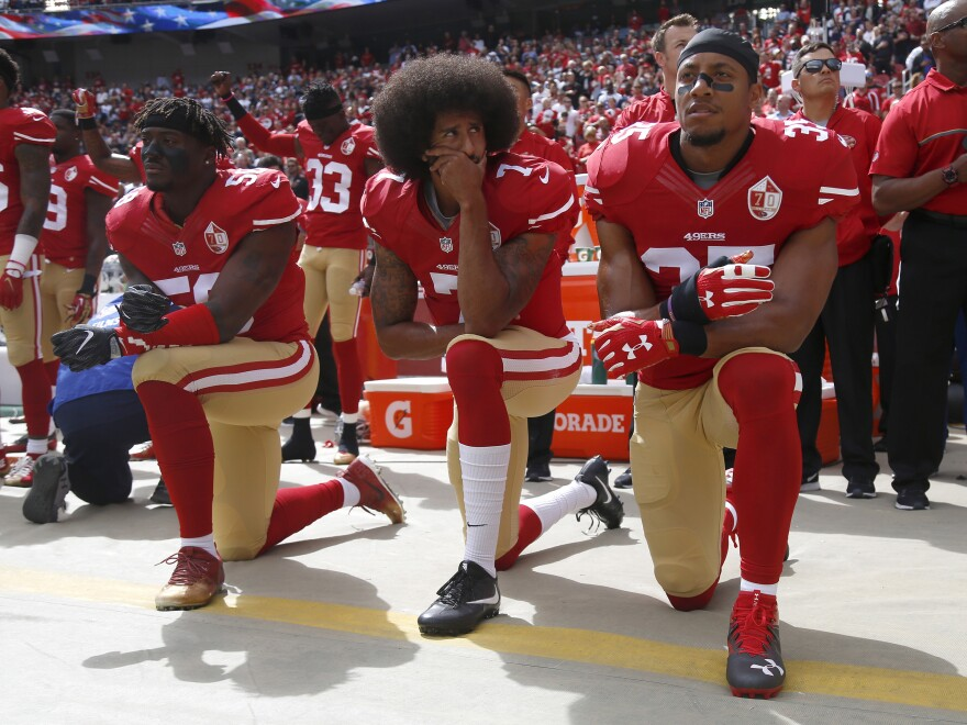 From left: Eli Harold (No. 58), Colin Kaepernick (No. 7) and Eric Reid (No. 35) kneel during the national anthem before their NFL game against the Dallas Cowboys on Oct. 2, 2016.