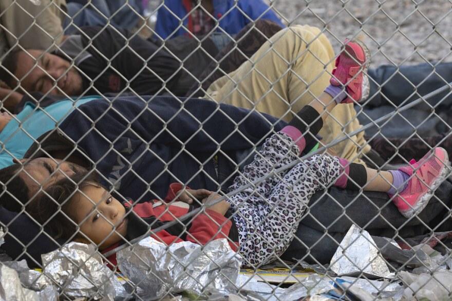 Migrants under a bridge