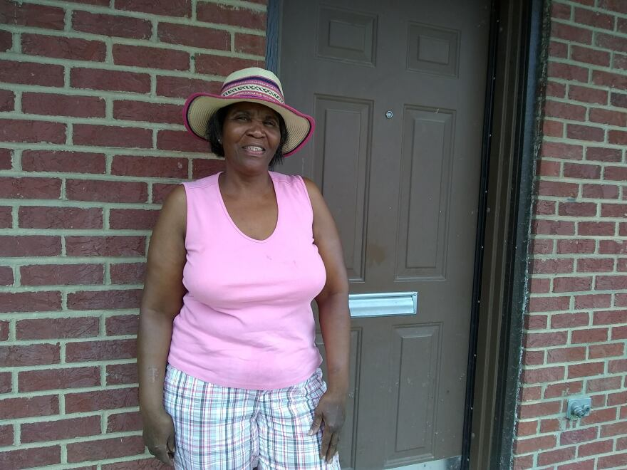 Artheia Jackson stands in front of her public housing home in East St. Louis one Saturday in July.