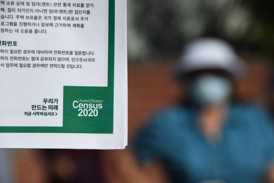 A volunteer displays information in Korean encouraging people to complete the US Census, at a food distribution bank for people facing economic hardship or food insecurity in a church parking lot in Los Angeles, California.