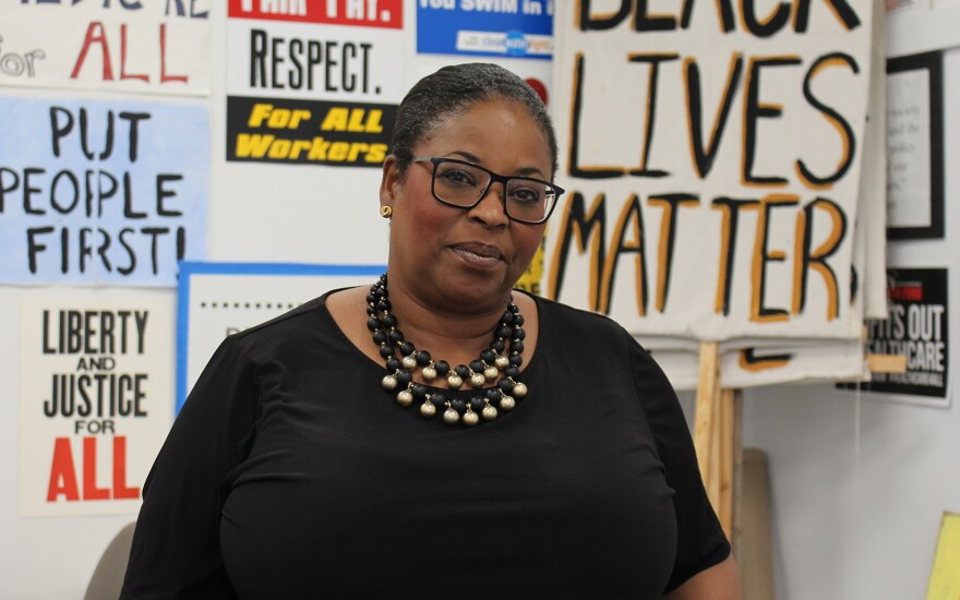 A portrait of Iowa CCI racial justice team member Lori Young with protest signs in the background.
