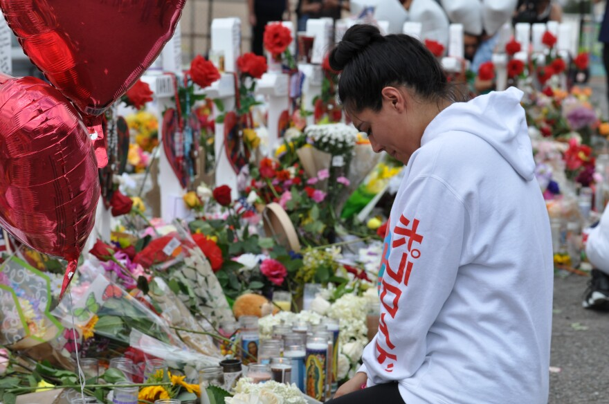 A women pauses at the memorial for the 22 people who died in a mass shooting in El Paso.
