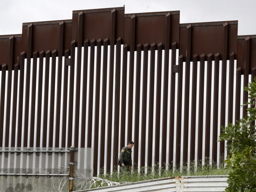 A border patrol agent walked along a border wall separating Tijuana, Mexico, from San Diego earlier this week.