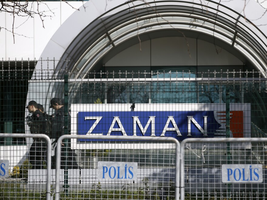 Riot police officers walk past the headquarters of <em>Zaman</em> newspaper, surrounded by police barriers in Istanbul, on March 6. Police used tear gas and water cannons to disperse hundreds of protesters who gathered in support of the paper outside its headquarters.