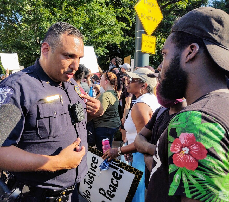 Officer Jesus Rendon of CMPD's Constructive Communication team talked with protester Joshua Bryant near police headquarters Tuesday.