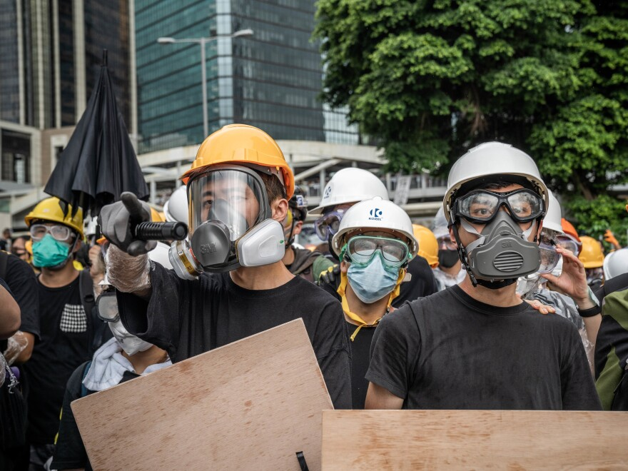 Anti-government protesters wear gas masks to protect themselves from possible tear gas and pepper spray on Aug. 17.