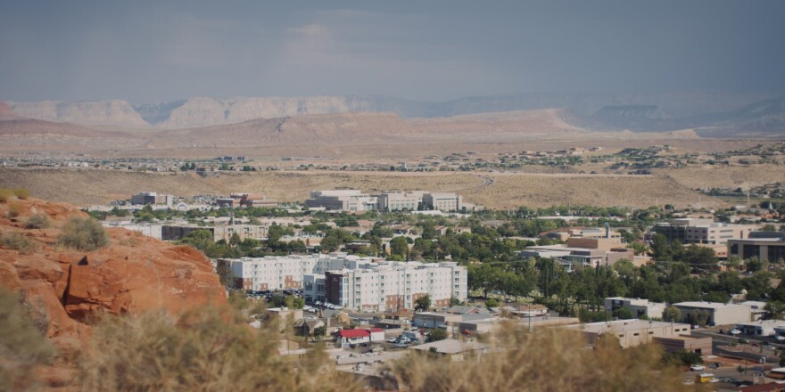 A city of white buildings is shown in the distance, sitting between red rock canyons and desert.