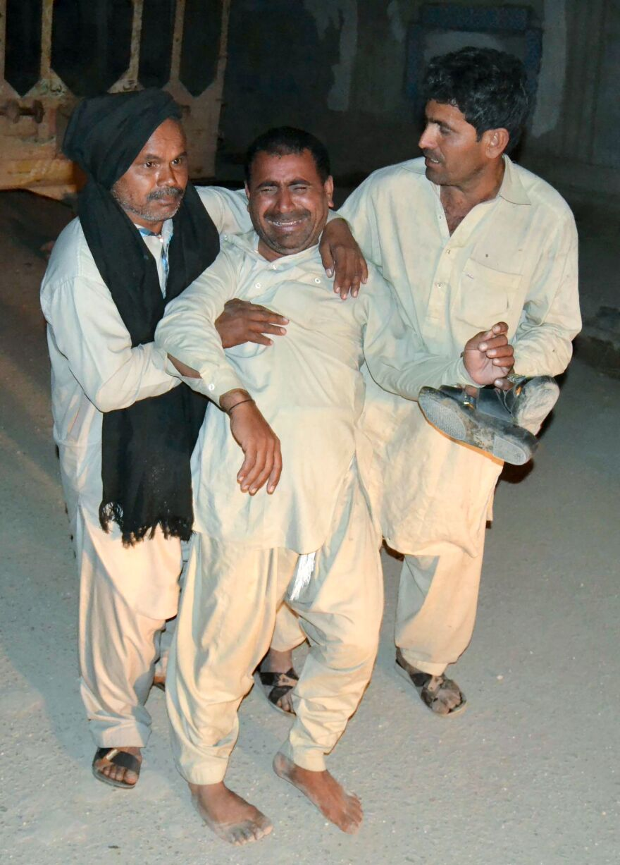 Two men comfort a mourner after the killing of his relative at the shrine Thursday.