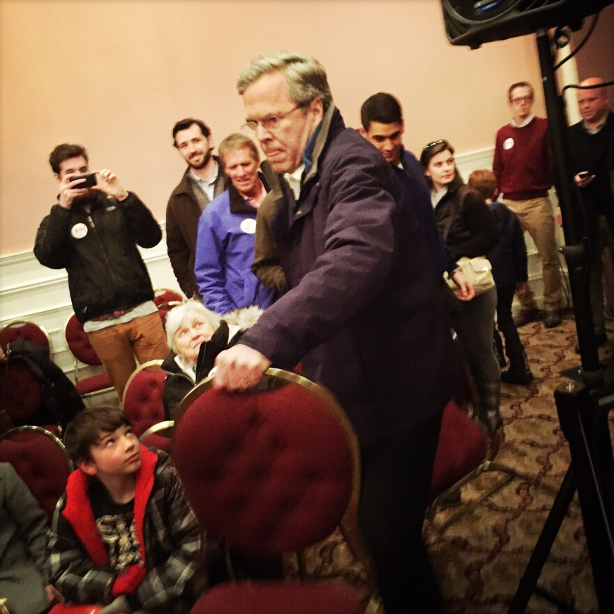 Bush helps put out additional chairs at his final New Hampshire town hall in Portsmouth on Monday evening.