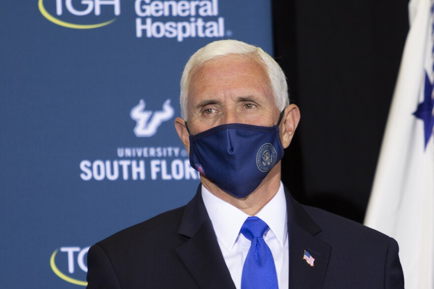 Vice President Mike Pence wearing a blue mask, looking to the right.