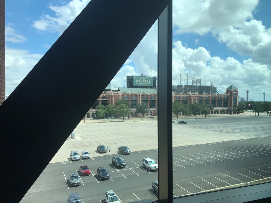 Out of a window, on a sunny day, a large brick stadium can be seen across a parking lot.