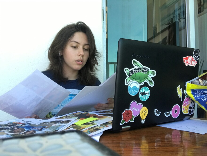 Brown haired girl looks at newspaper by computer