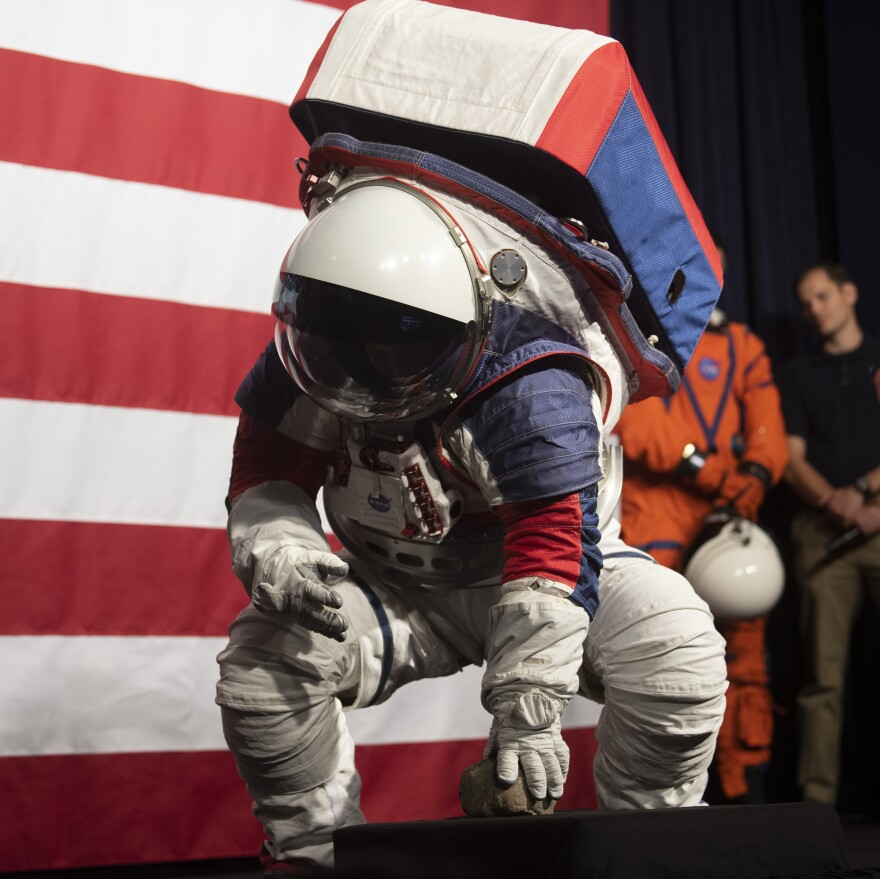 Kristine Davis bends down to pick up a rock during a demonstration of the mobility of the Exploration Extravehicular Mobility Unit (xEMU), one of two NASA spacesuit prototypes for lunar exploration.