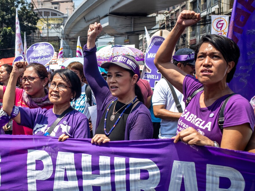 Leaders of various women's groups raise their fists as they march near the Malacanang presidential palace to mark International Women's Day Sunday in Manila, Philippines.