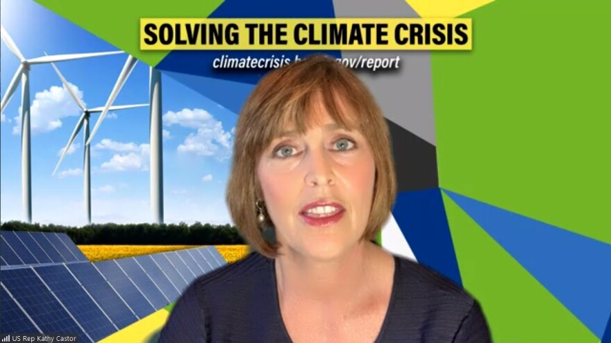 "Rep. Kathy Castor of Tampa talking in front of an image of wind turbines and solar panels. Above her reads, ""Solving The Climate Crisis."""