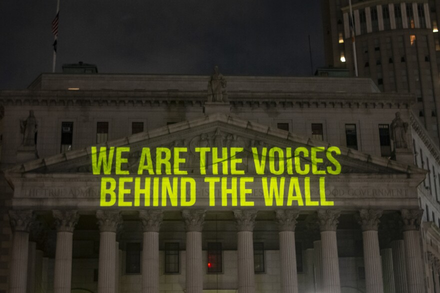 """The Writing On The Wall"" art installation projects writings by incarcerated people onto the sides of buildings, such as The New York State Supreme Court Building, above."