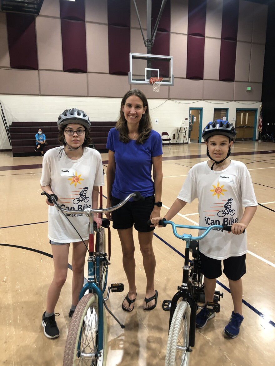A lady standing with two kids wearing helmets next to their bikes.
