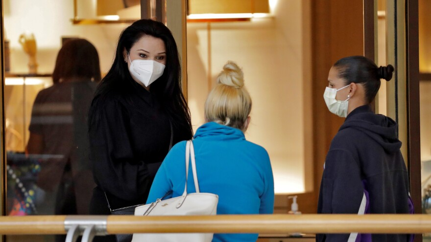 A salesperson left, wears a protective face mask as she talks to customers at the International Mall Wednesday, May 6, 2020, in Tampa, Fla.
