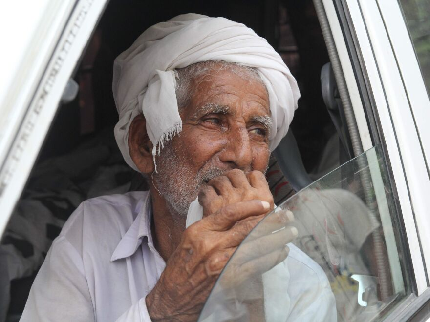 Muhammad Azeem, Qandeel Baloch's father, sits in an ambulance carrying the body of his daughter on July 17. He has called for his son to be punished for committing the murder.